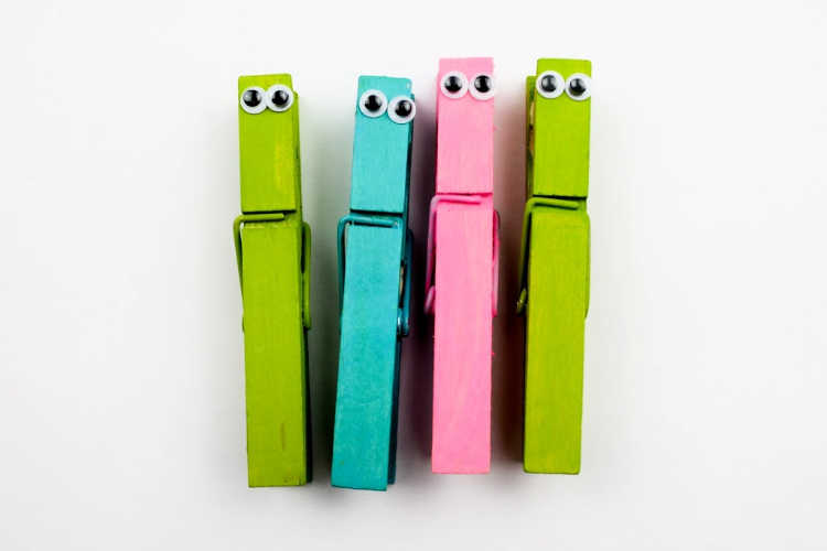 Adding googly eyes to the clothes pins to make butterflies - DIY butterfly craft for kids at DearCreatives.com