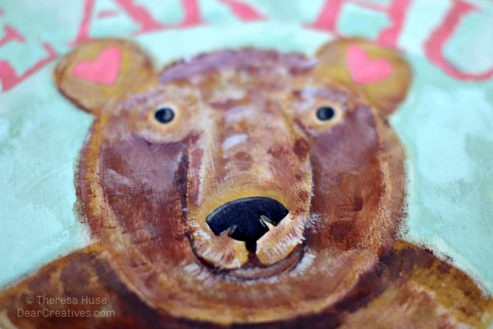 Detailing-bear-face-with-black-nose-eyes-and-toffee-highlights. Acrylic paint step by step how-to paint a cute bear face. DearCreatives.com