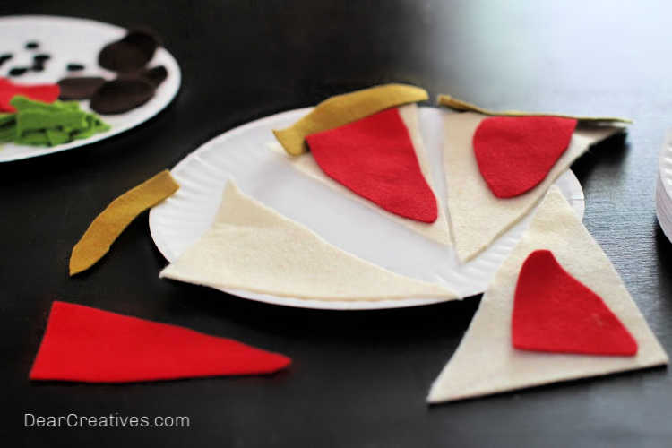 We cut out these felt shapes by hand. We made templates for the pizza toppings and pizza. They are free printables for making the felt pizza. Find instructions and template at DearCreatives.com